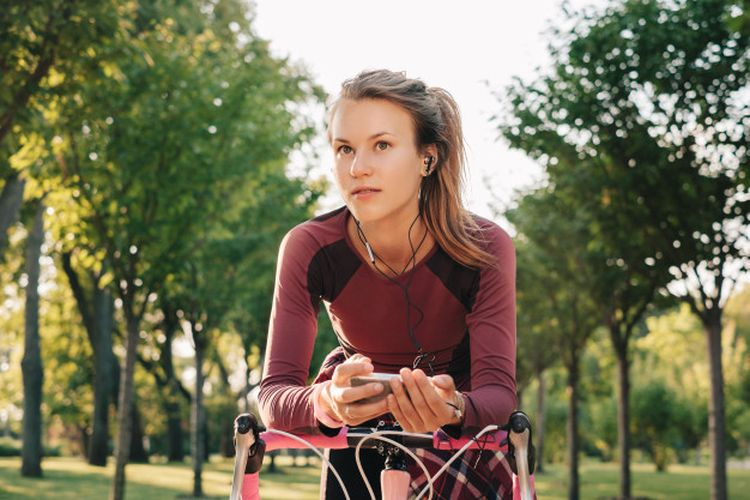 sport woman cycling with music